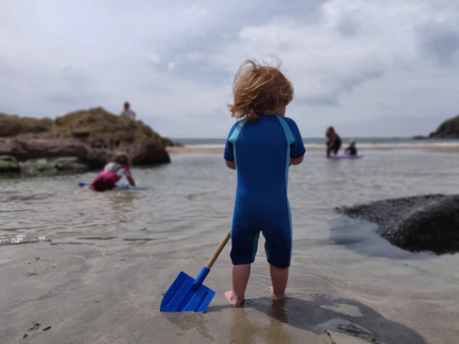 Child standing on a beach in Pembrokeshire facing the sea